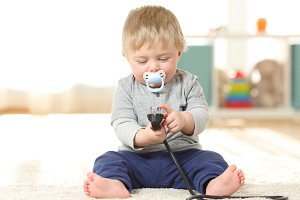 Baby in danger playing with a plug