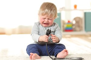 Baby crying holding an an plug