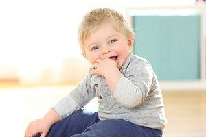 Baby biting finger looking at camera