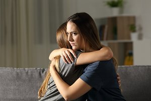 Angry woman hugging a friend at home