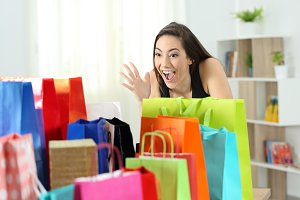 Amazed woman looking at multiple bag