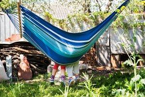 Children's feet in blue hammock on a