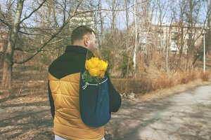 Young adult man carrying a backpack