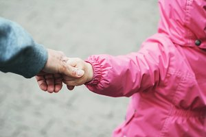 A little girl leads by the hand of h