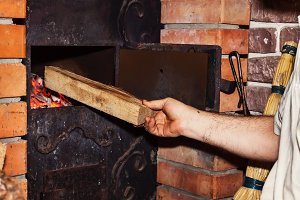Man puts firewood in a stove, close-