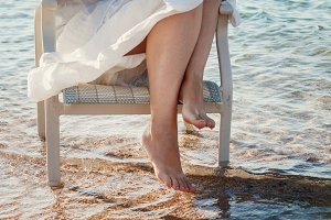Bare legs girl in a white dress touc