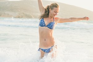 Young woman jumping in wavy waters