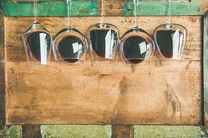 Red wine in glasses over wooden tray