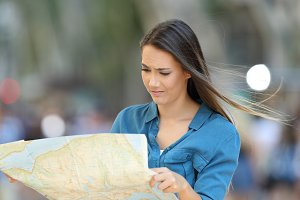 Confused lost tourist reading a map