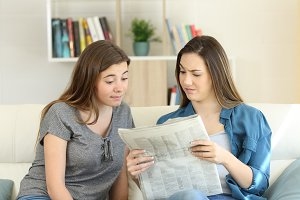 Confused friends reading newspaper