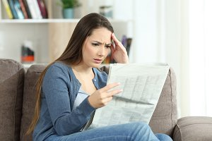 Concerned woman reading a newspaper