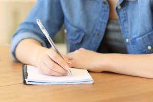Girl writing notes in a notebook