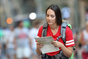Frustated teen tourist reading a map