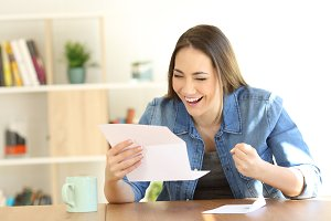 Excited woman reading good news in a