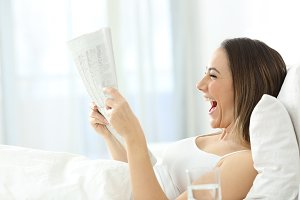 Excited woman reading a newspaper