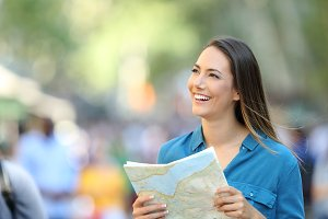 Happy tourist sightseeing with a map