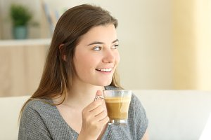 Happy teen drinking coffee with milk