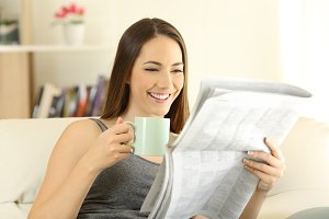 Happy female reading a newspaper