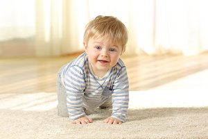 Happy baby crawling towards camera