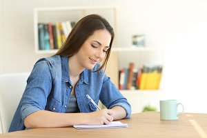 Girl writing in a notebook at home