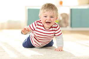 Joyful baby crawling towards camera