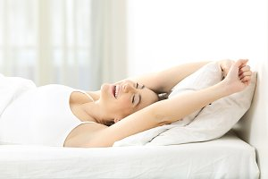 Happy woman waking up stretching arm