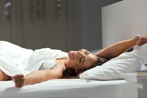 Happy woman stretching arms on a bed