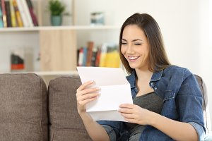 Happy woman reading a letter