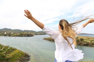 Happy woman raising arms to the wind