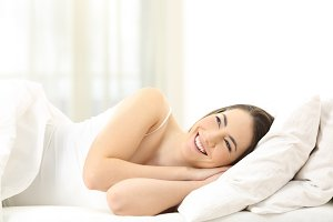 Happy woman lying on a bed