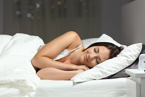Happy woman sleeping on the bed