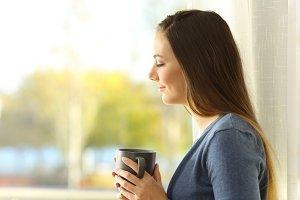Pensive lady holding a coffee mug