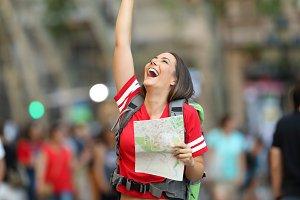 Joyful teen tourist holding a map