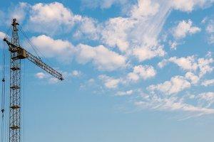 Construction crane on cloud sky back