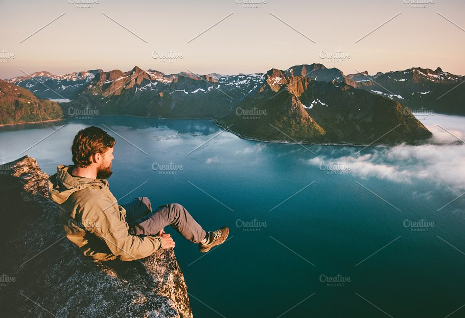 man sitting alone on the edge cliff people images creative market