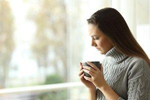Sad melancholic woman holding a mug
