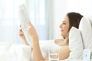 Relaxed woman reading a newspaper