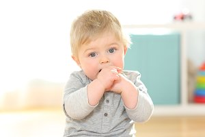 Portrait of a kid biting his fingers