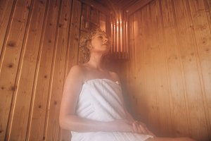 Woman sitting in a wooden sauna spa