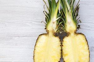 Flat lay of pineapple cut in half.