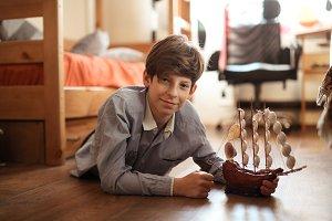 teen plays with ship model on floor