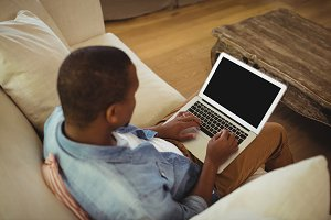 Man sitting on sofa and using laptop