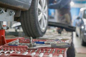 Mechanic tools lie next to the car's
