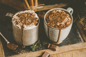 Tasty hot chocolate drink in mugs