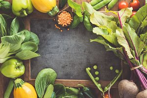 Fresh vegetables with board on woode