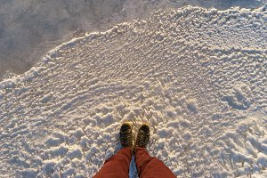 Male legs standing on scenic icy