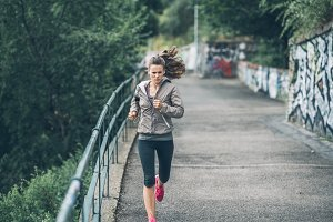Fitness young woman jogging in the c