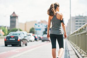 Fitness young woman walking in the c
