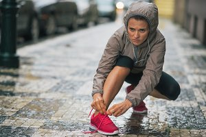 Fitness young woman tying shoelaces
