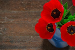 Red tulips on an antique wooden background